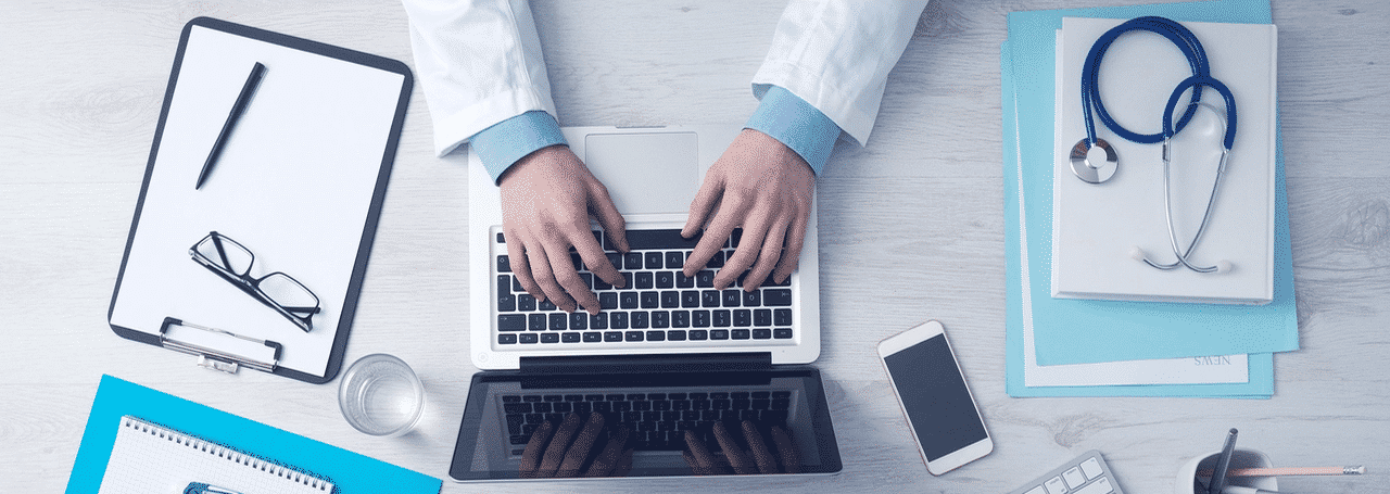 Doctor's hands typing on laptop. Photo.